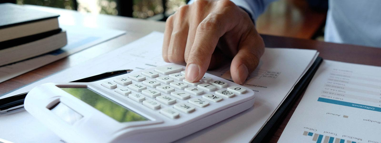Man using calculator to work out finances for reverse VAT charge