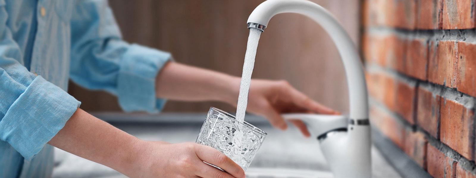 Woman pouring a drink from a tap and not wasting water