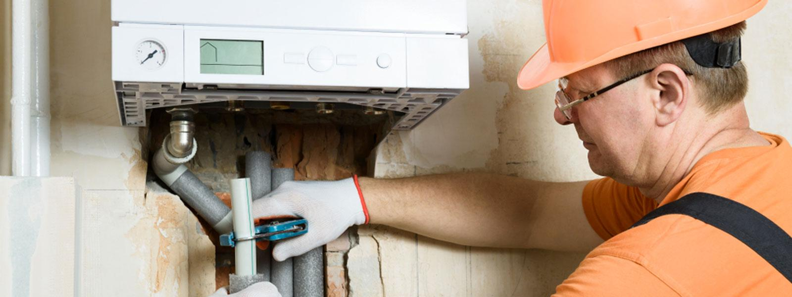 Plumber fixing boiler - Key signs your home utilities systems are on the way out