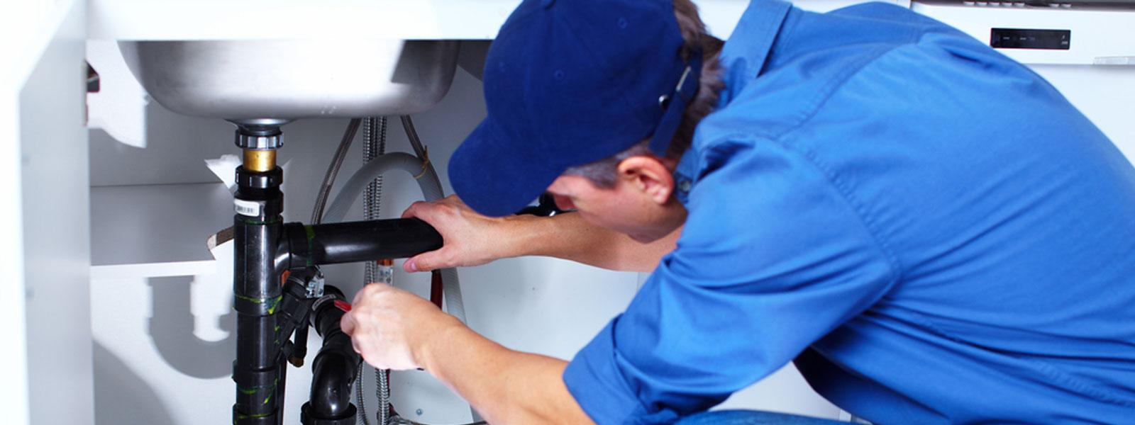 self-employed plumber plumbing in a sink