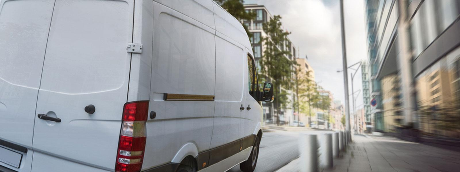 White van driving through a city