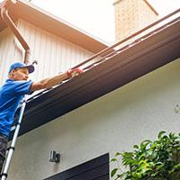 Tradesperson cleaning gutters