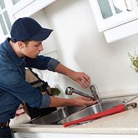 self-employed plumber fixing sink