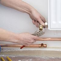 A plumber that has taken on self-employment fixing a radiator