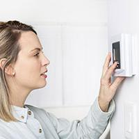 Woman saving hundreds of pounds by turning down the thermostat from Energy Supplier